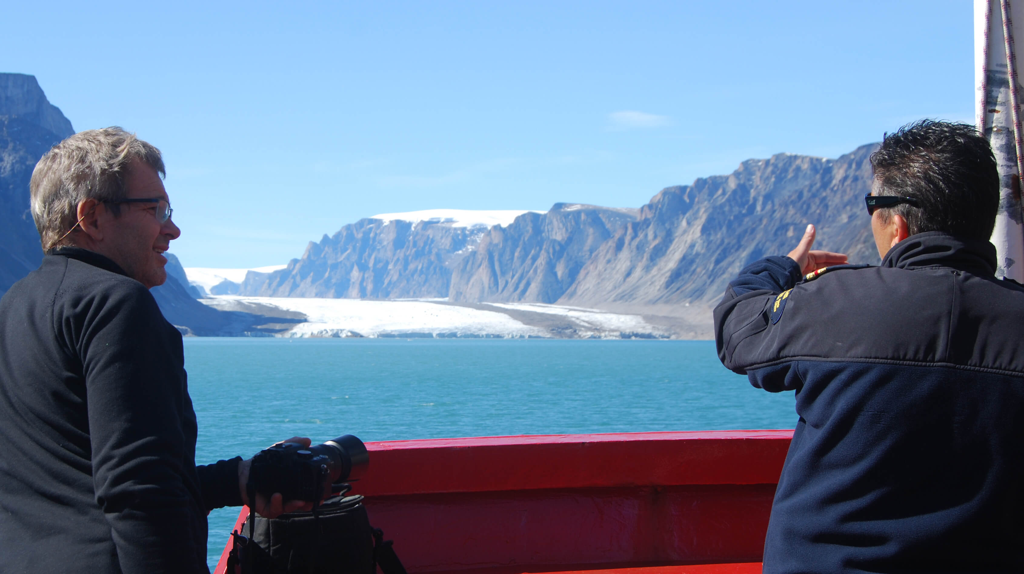 Mentor Marc Picheral discussing glacier features with a coast guard officer  - Sentinel North international phd school